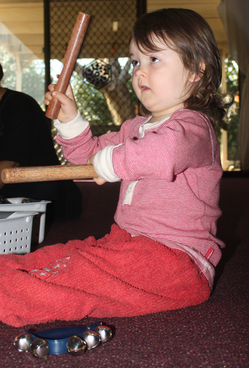 child playing claves